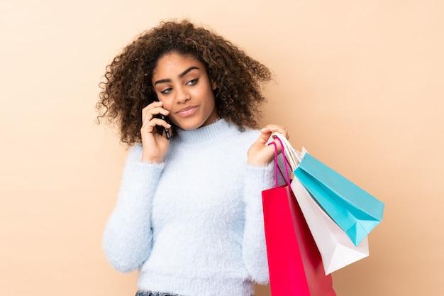 Młoda amerykanin afrykańskiego pochodzenia kobieta na beż ścianie trzyma torby na zakupy i dzwoni przyjacielu z jej telefonem komórkowym