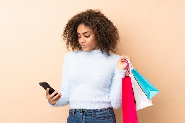 Młoda amerykanin afrykańskiego pochodzenia kobieta na beż ścianie trzyma torby na zakupy i pisze wiadomości z jej telefonem komórkowym
