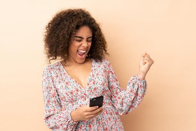 Młoda amerykanin afrykańskiego pochodzenia kobieta na beż ścianie z telefonem w zwycięstwo pozyci