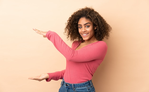 Młoda amerykanin afrykańskiego pochodzenia kobieta na beżowej ścianie trzyma pustą przestrzeń, aby wstawić reklamę