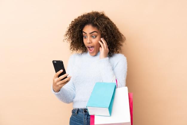 Młoda amerykanin afrykańskiego pochodzenia kobieta na beżowej ścianie trzyma torba na zakupy i pisze wiadomości z jej telefonem komórkowym przyjacielowi