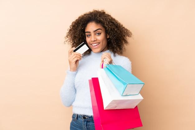 Młoda amerykanin afrykańskiego pochodzenia kobieta na beżowej ściany mienia torba na zakupy i karcie kredytowej