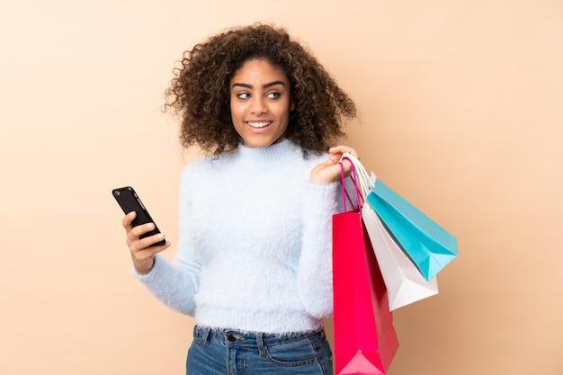 Młoda amerykanin afrykańskiego pochodzenia kobieta na beżowej ściany mienia torba na zakupy i telefonie komórkowym