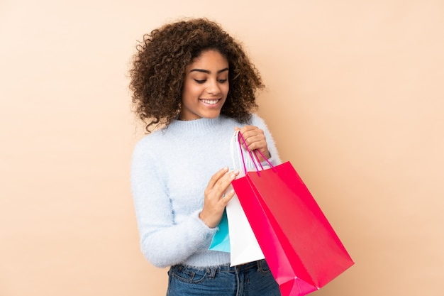 Młoda amerykanin afrykańskiego pochodzenia kobieta na beżowej ściany mienia torba na zakupy