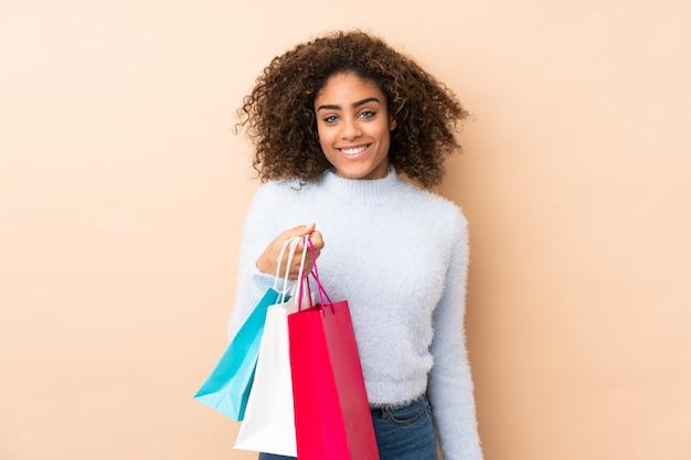 Młoda amerykanin afrykańskiego pochodzenia kobieta na beżu ściany mienia torba na zakupy i główkowaniu