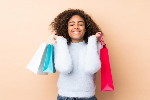 Młoda amerykanin afrykańskiego pochodzenia kobieta na beżu ściany mienia torba na zakupy i ono uśmiecha się