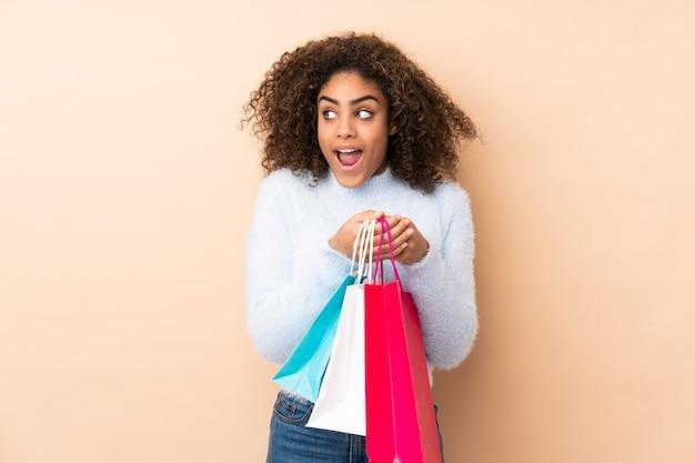Młoda amerykanin afrykańskiego pochodzenia kobieta na beżu ściany mienia torba na zakupy i zaskakujący