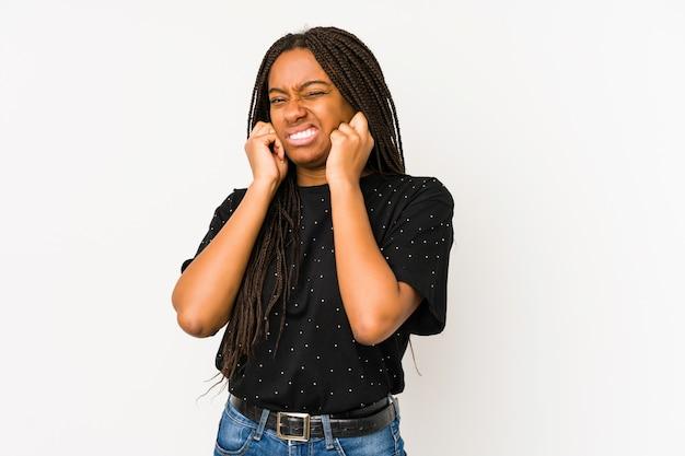 Młoda amerykanin afrykańskiego pochodzenia kobieta na biel ściany nakrywkowych ucho z rękami.