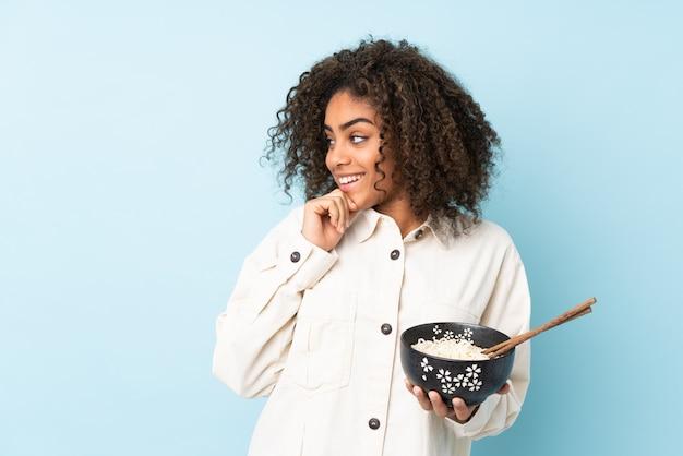 Młoda amerykanin afrykańskiego pochodzenia kobieta na błękit ścianie myśleć pomysł i patrzeje stronę podczas gdy trzymający puchar kluski pałeczkami