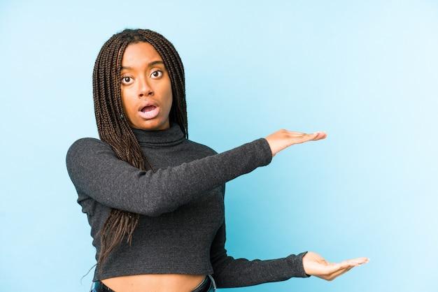 Młoda amerykanin afrykańskiego pochodzenia kobieta na błękit ścianie szokuje i zadziwia trzymający pustą przestrzeń między rękami.