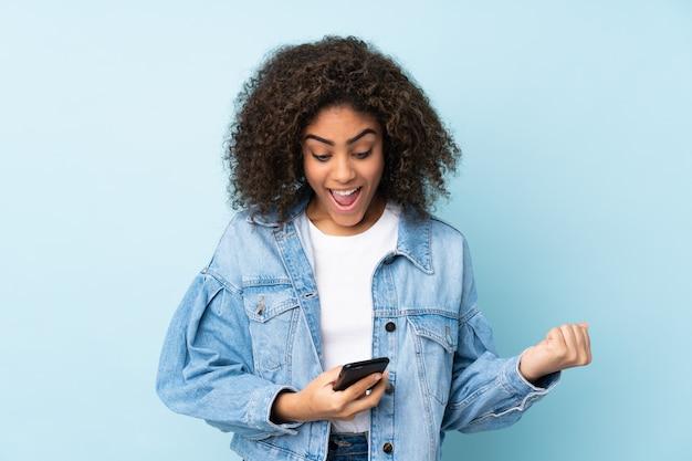 Młoda amerykanin afrykańskiego pochodzenia kobieta na błękit ścianie zaskakująca i wysyła wiadomość