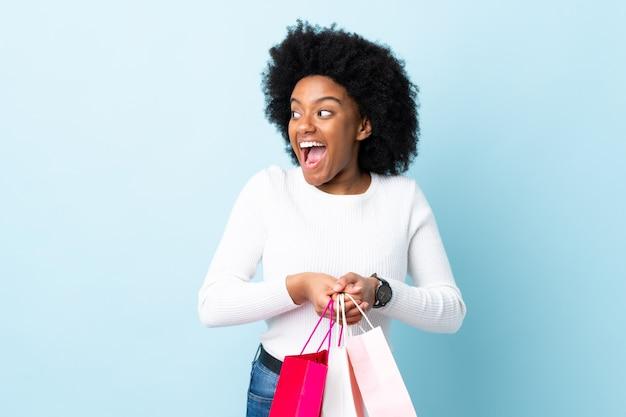 Młoda amerykanin afrykańskiego pochodzenia kobieta na błękit ściany mienia torba na zakupy i zaskakujący