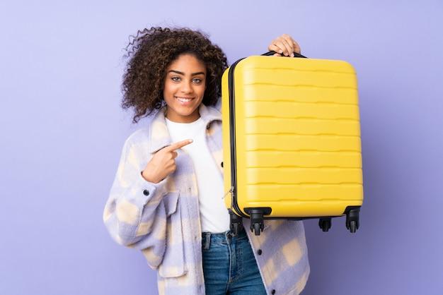 Młoda amerykanin afrykańskiego pochodzenia kobieta na purpurach izoluje w wakacje z podróży walizką