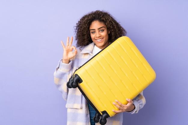 Młoda amerykanin afrykańskiego pochodzenia kobieta na purpury ścianie w wakacje z podróży walizką i robić ok znakowi