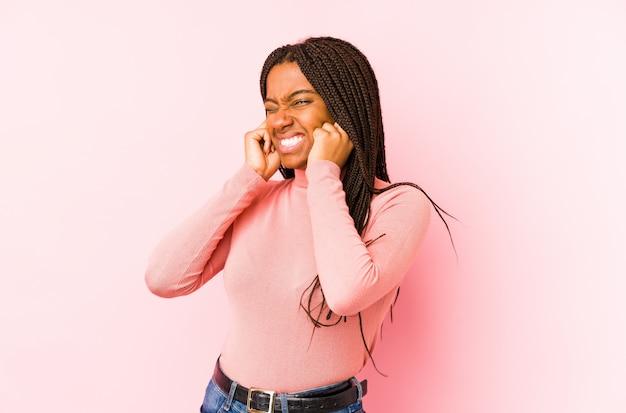 Młoda amerykanin afrykańskiego pochodzenia kobieta na różowej ściennej nakrywkowej ucho z rękami.