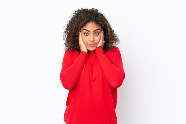 Młoda amerykanin afrykańskiego pochodzenia kobieta na ścianie udaremniał i zakrywa ucho