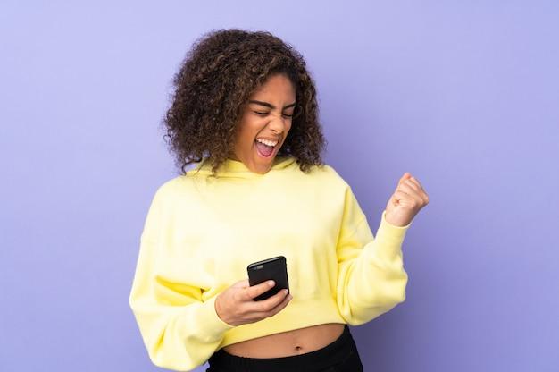 Młoda amerykanin afrykańskiego pochodzenia kobieta na ścianie z telefonem w zwycięstwo pozyci