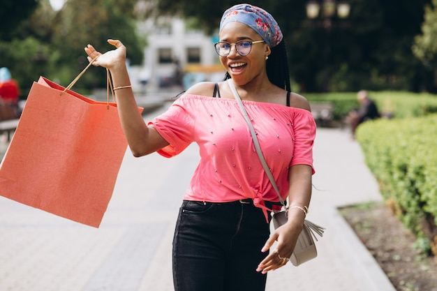 Młoda amerykanin afrykańskiego pochodzenia kobieta na ulicie z torba na zakupy