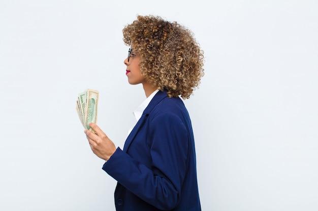 Młoda amerykanin afrykańskiego pochodzenia kobieta na widoku profilu patrzeje kopiować przestrzeń naprzód, myśleć, wyobraża sobie lub marzy z banknotami euro