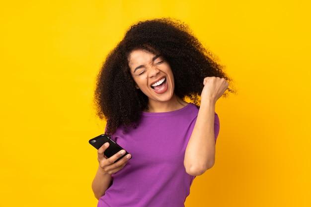 Młoda amerykanin afrykańskiego pochodzenia kobieta nad ścianą z telefonem w zwycięstwo pozyci