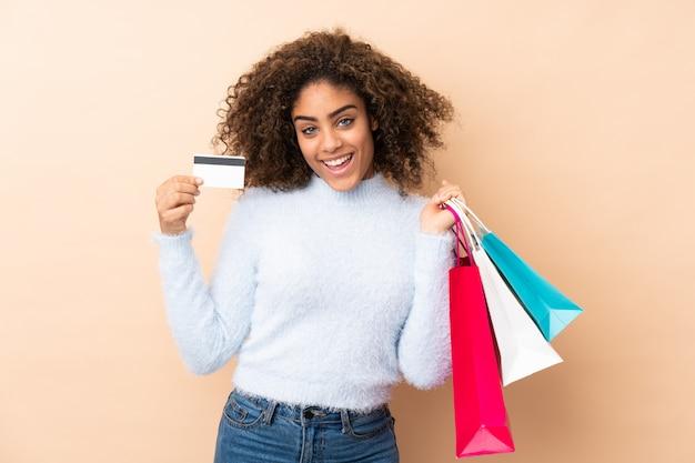 Młoda amerykanin afrykańskiego pochodzenia kobieta odizolowywająca na beżowych mień torba na zakupy i karcie kredytowej