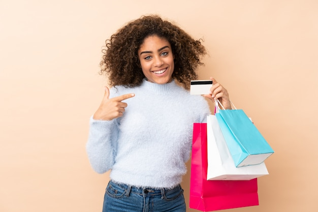 Młoda amerykanin afrykańskiego pochodzenia kobieta odizolowywająca na beżu przestrzeni mienia torba na zakupy i karcie kredytowej