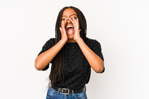 Młoda amerykanin afrykańskiego pochodzenia kobieta odizolowywająca na biel ścianie krzyczy podekscytowany do przodu.