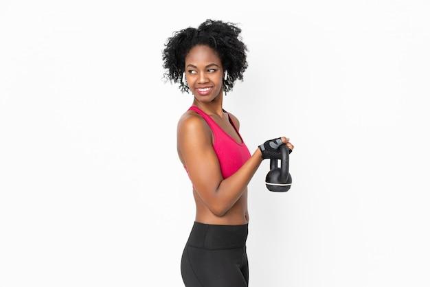 Młoda amerykanin afrykańskiego pochodzenia kobieta odizolowywająca na biel ścianie robi ciężarowi z kettlebell