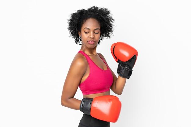 Młoda amerykanin afrykańskiego pochodzenia kobieta odizolowywająca na biel ścianie z bokserskimi rękawiczkami