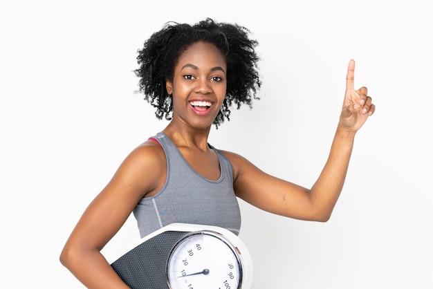 Młoda amerykanin afrykańskiego pochodzenia kobieta odizolowywająca na biel ścianie z ważyć maszynę
