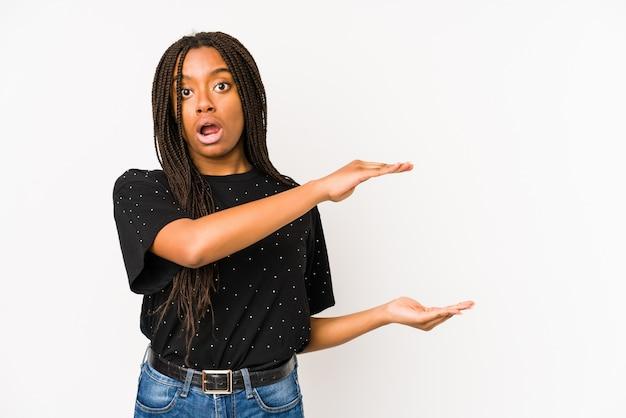 Młoda amerykanin afrykańskiego pochodzenia kobieta odizolowywająca na biel ścianie zszokował i zadziwiał trzymający odbitkową przestrzeń między rękami.