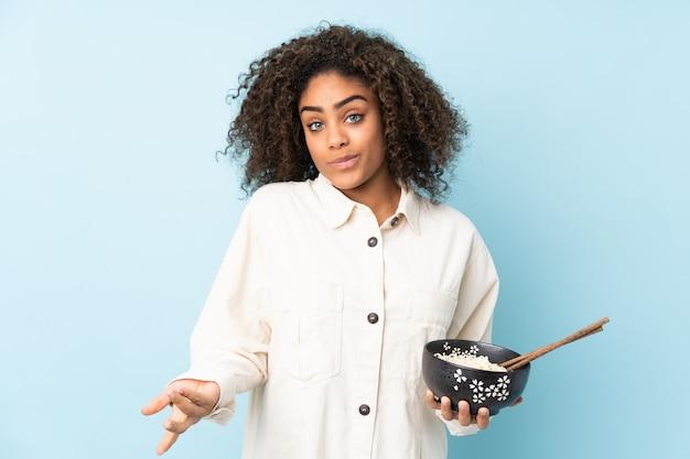 Młoda amerykanin afrykańskiego pochodzenia kobieta odizolowywająca na błękicie robi wątpliwościom gestykuluje podczas gdy podnoszący ramiona podczas gdy trzymający puchar kluski z chopsticks