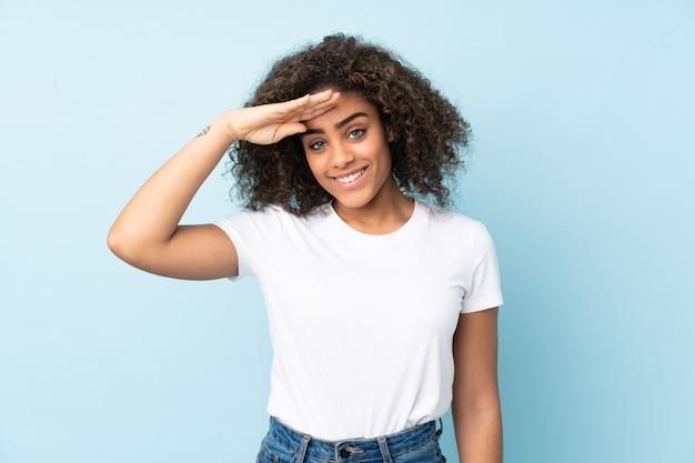 Młoda amerykanin afrykańskiego pochodzenia kobieta odizolowywająca na błękicie salutuje z ręką z szczęśliwym wyrażeniem