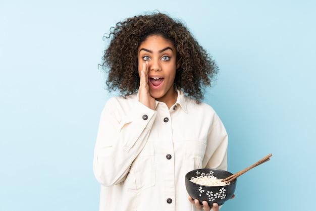 Młoda amerykanin afrykańskiego pochodzenia kobieta odizolowywająca na błękit przestrzeni krzyczy z usta szeroko otwarty, podczas gdy trzymający puchar kluski z pałeczkami