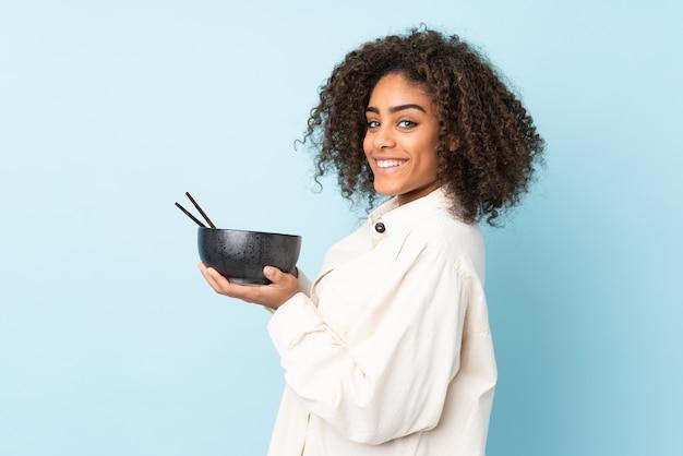 Młoda amerykanin afrykańskiego pochodzenia kobieta odizolowywająca na błękit przestrzeni trzyma puchar kluski z pałeczkami