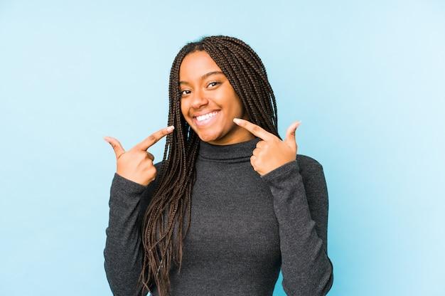 Młoda amerykanin afrykańskiego pochodzenia kobieta odizolowywająca na błękit ścianie ono uśmiecha się, wskazujący palce przy usta.