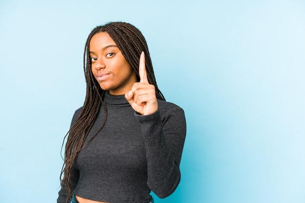 Młoda amerykanin afrykańskiego pochodzenia kobieta odizolowywająca na błękit ścianie pokazuje liczbę jeden z palcem.