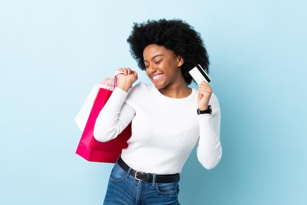 Młoda amerykanin afrykańskiego pochodzenia kobieta odizolowywająca na błękit ścianie trzyma torby na zakupy i kartę kredytową