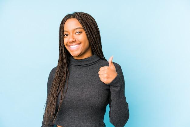 Młoda amerykanin afrykańskiego pochodzenia kobieta odizolowywająca na błękit ścianie uśmiecha się kciuk up i podnosi