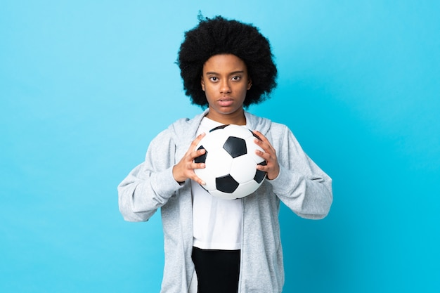 Młoda amerykanin afrykańskiego pochodzenia kobieta odizolowywająca na błękit ścianie z piłki nożnej piłką