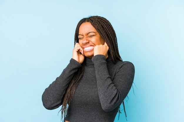 Młoda amerykanin afrykańskiego pochodzenia kobieta odizolowywająca na błękit ściany nakrywkowych ucho z rękami.