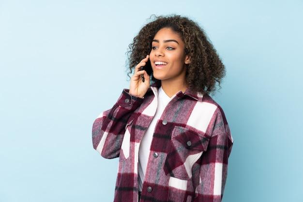 Młoda amerykanin afrykańskiego pochodzenia kobieta odizolowywająca na błękitnej przestrzeni utrzymuje rozmowę z telefonem komórkowym