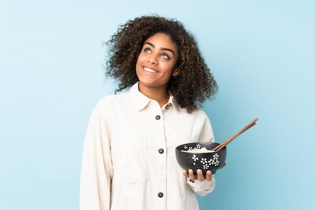 Młoda amerykanin afrykańskiego pochodzenia kobieta odizolowywająca na błękitny przyglądającym up podczas gdy ono uśmiecha się podczas gdy trzymający puchar kluski z chopsticks