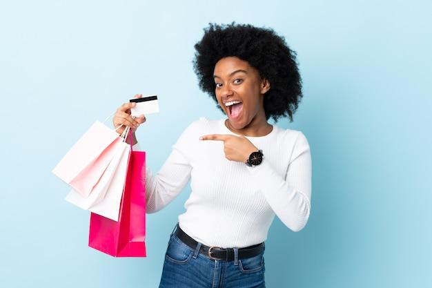 Młoda amerykanin afrykańskiego pochodzenia kobieta odizolowywająca na błękitnym tła mienia torba na zakupy i karcie kredytowej