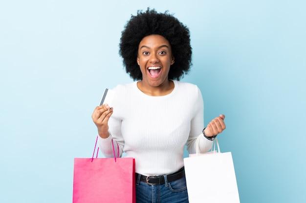 Młoda amerykanin afrykańskiego pochodzenia kobieta odizolowywająca na błękitnym tła mienia torba na zakupy i zaskakująca
