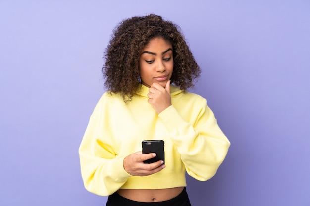 Młoda amerykanin afrykańskiego pochodzenia kobieta odizolowywająca na główkowaniu i wysyłaniu wiadomość