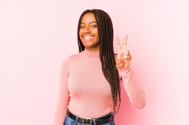 Młoda amerykanin afrykańskiego pochodzenia kobieta odizolowywająca na różowej ścianie pokazuje zwycięstwo znaka i uśmiecha się szeroko.