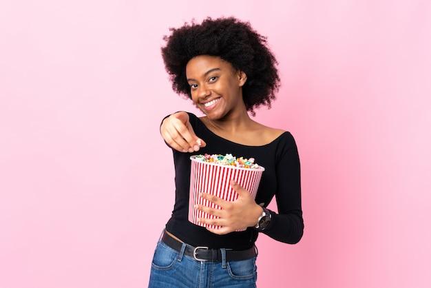 Młoda amerykanin afrykańskiego pochodzenia kobieta odizolowywająca na różowym tle trzyma dużego wiadro popkorny podczas gdy wskazujący przód