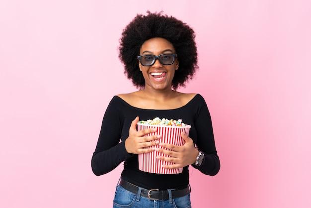 Młoda amerykanin afrykańskiego pochodzenia kobieta odizolowywająca na różowym tle z 3d szkłami i trzymający dużego wiadro popkorn