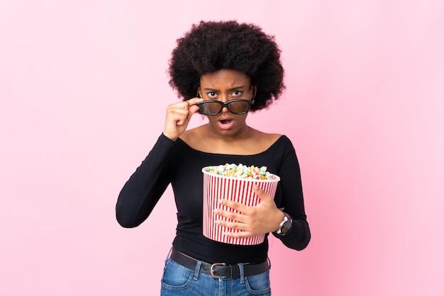 Młoda amerykanin afrykańskiego pochodzenia kobieta odizolowywająca na różowym tle zaskakującym z 3d szkłami i trzymający dużego wiadro popcorns